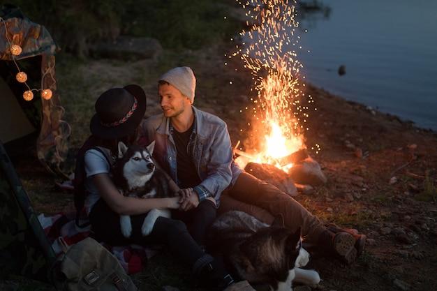 Couple se regardant avec des chiens tente nature