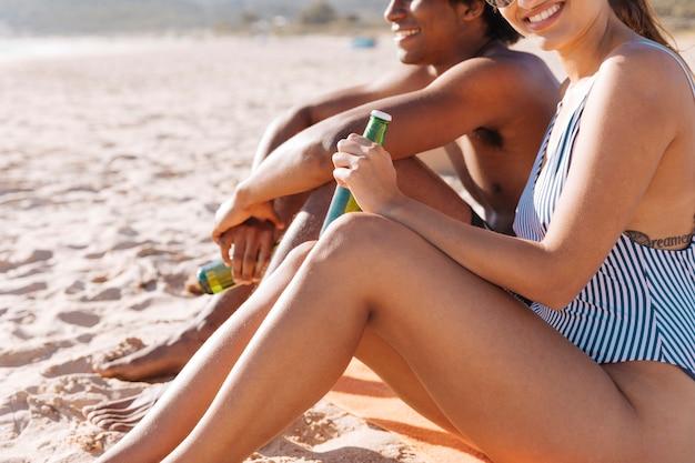Couple se reposant sur la plage avec des boissons