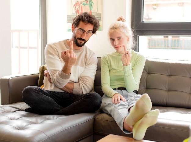 Couple se sentant en colère, ennuyé, rebelle et agressif, retournant le majeur, ripostant