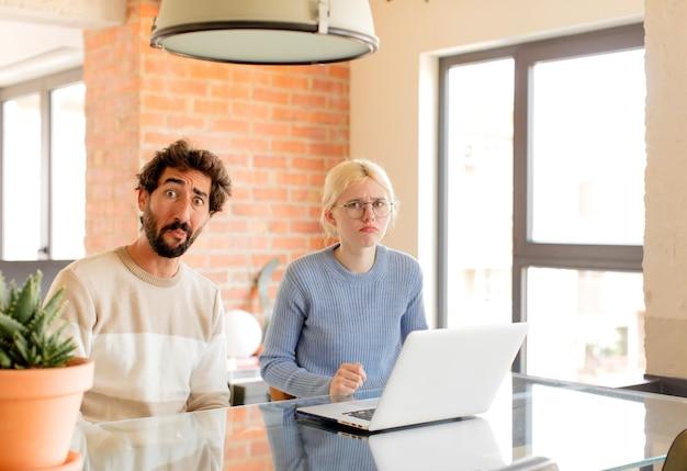 Couple se sentant triste et pleurnichard avec un regard malheureux, pleurant avec une attitude négative et frustrée