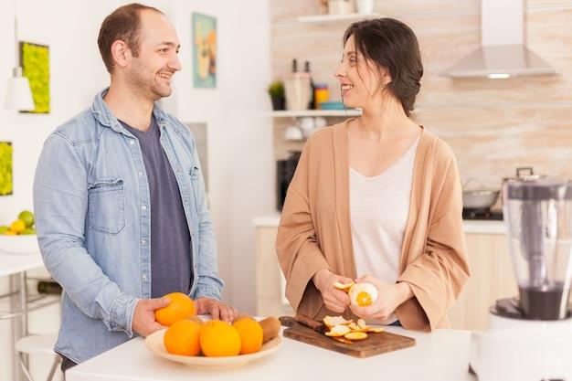 Couple se souriant tout en préparant un smoothie nutritif. femme décollant l'orange. mode de vie sain, insouciant et joyeux, régime alimentaire et préparation du petit-déjeuner dans une agréable matinée ensoleillée