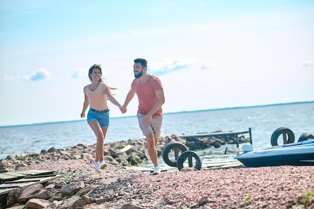 Un couple se tenant la main et courant sur une plage