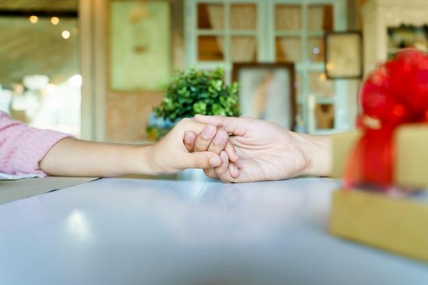 Un couple se tenant les mains dans un restaurant avec une boîte-cadeau en or avec un ruban rouge.