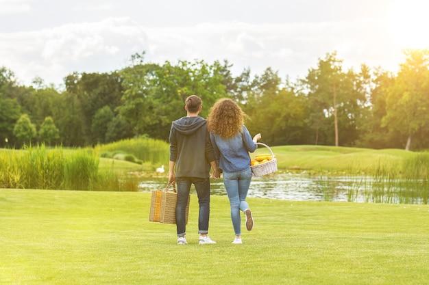 Le couple se tient sur l'herbe dans le contexte de la rivière