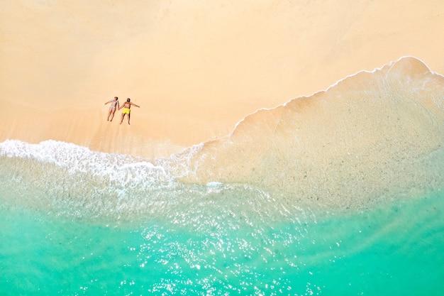 Un couple se trouve sur la plage de l'île maurice dans l'océan indien. vue de dessus de la plage aux eaux turquoises sur l'île tropicale de l'ile maurice