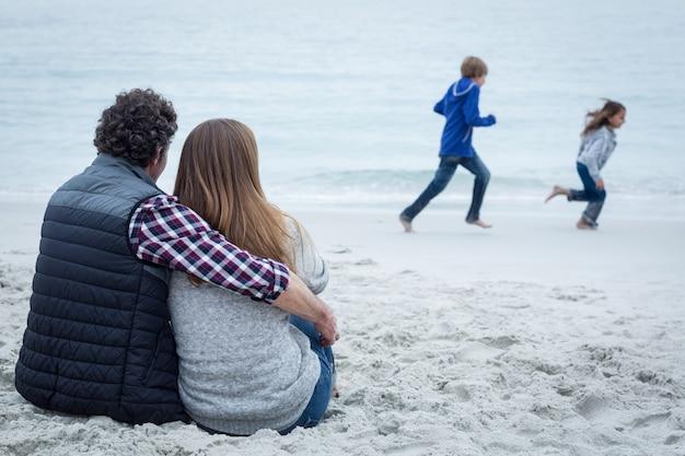 Couple, séance, enfants, jouer, bord mer