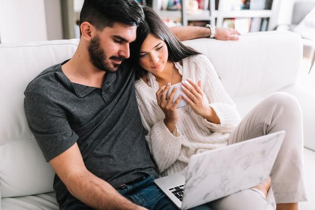 Couple, séance, sofa, regarder, ordinateur portable