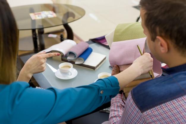 Couple sélectionne des tissus dans sa nouvelle maison avec un architecte d'intérieur.