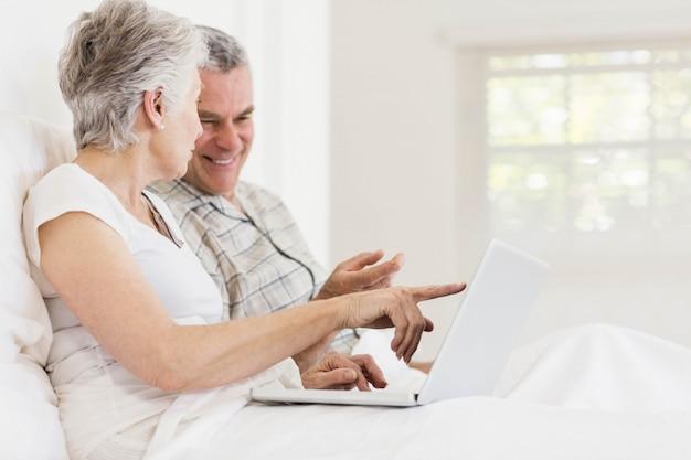 Couple senior à l'aide d'un ordinateur portable assis sur le lit
