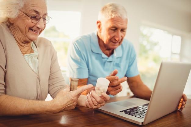 Couple senior à l'aide d'un ordinateur portable et tenant des pilules à la maison