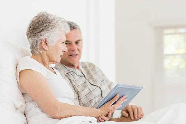 Couple senior à l'aide de tablette assis sur le lit