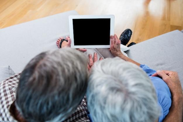 Couple senior à l'aide d'une tablette numérique sur un canapé