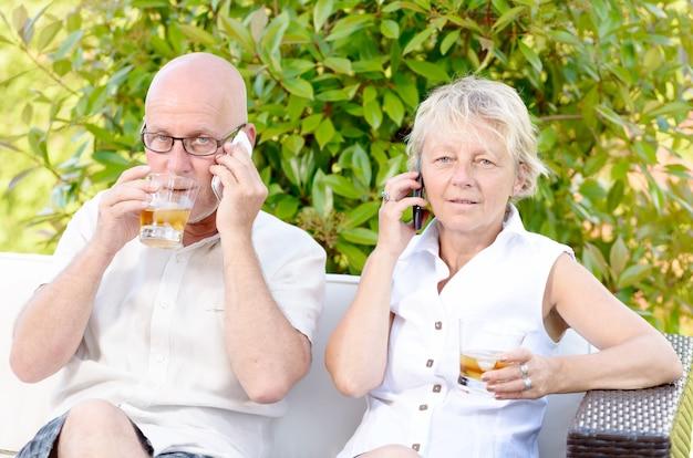 Couple senior assis sur un canapé, buvant un verre d'alcool