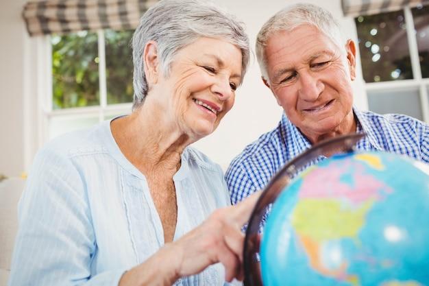 Couple senior assis sur un canapé et regardant un globe dans le salon