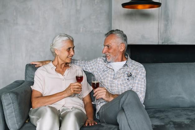 Couple senior assis sur le canapé tenant un verre de vin
