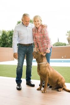 Couple senior avec chien dans le jardin