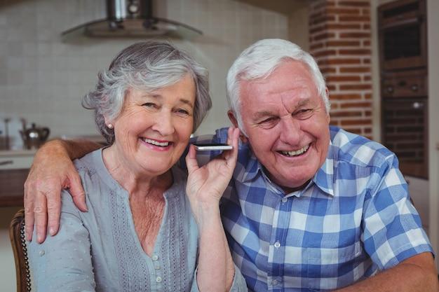 Couple senior à l'écoute de la musique dans la cuisine