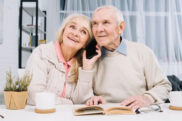 Couple senior à l'écoute de smartphone