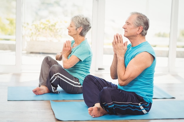 Couple senior effectuant le yoga