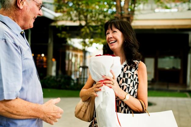 Couple senior femme tenant un bouquet de roses