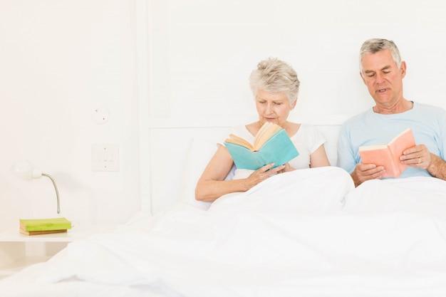 Couple senior lire des livres au lit