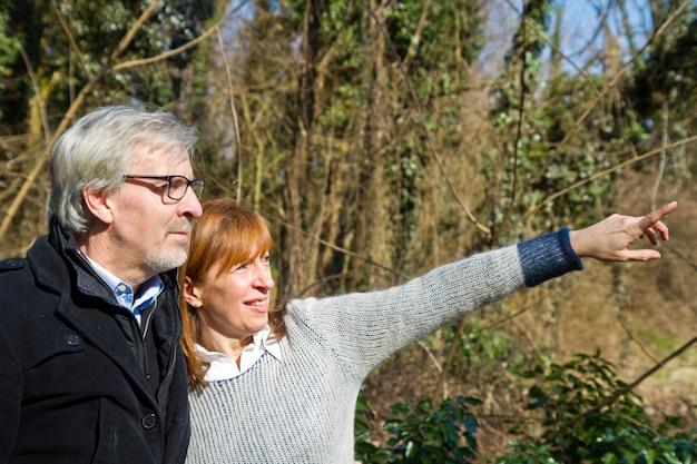 Couple senior montrant quelque chose dans le parc