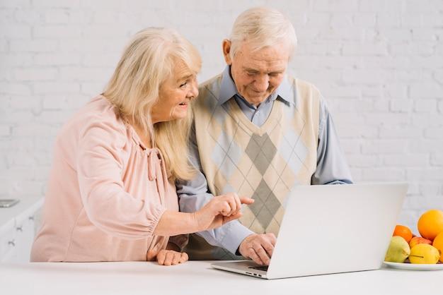 Couple senior avec ordinateur portable dans la cuisine