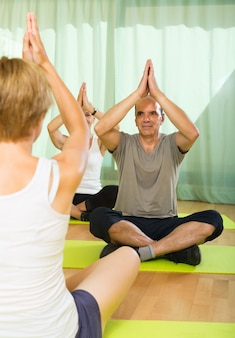 Couple senior pratiquant le yoga avec instructeur