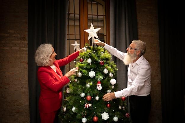 Couple senior prépare l'arbre de noël