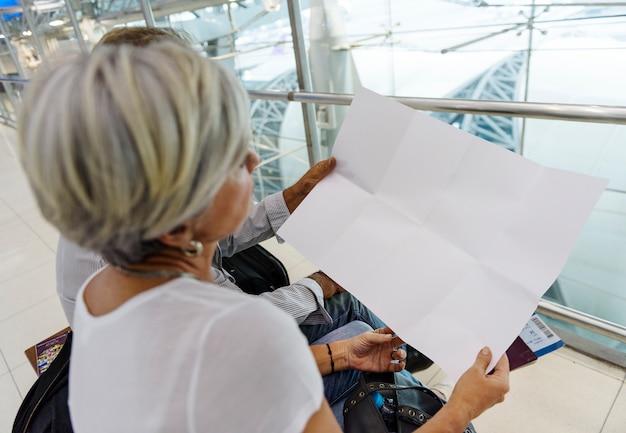Couple senior à la recherche à l'aéroport de papier vierge