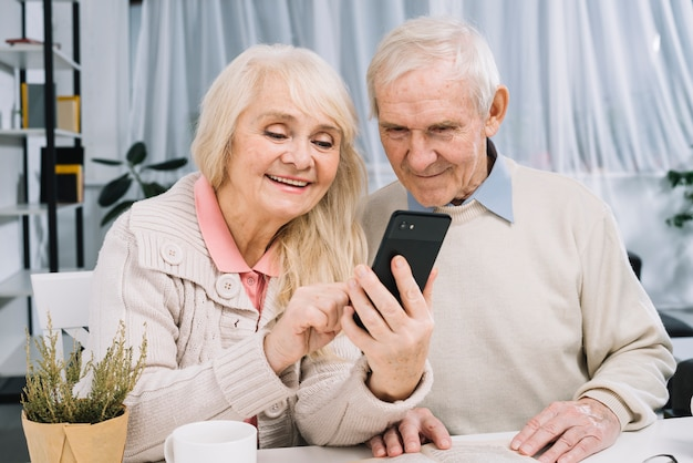Couple senior à la recherche de smartphone