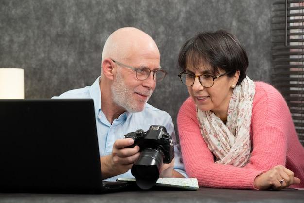 Couple senior en regardant des photos de vacances sur la caméra