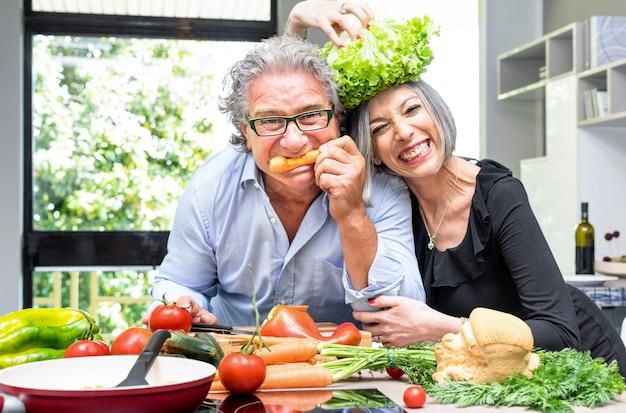 Couple senior s'amuser dans la cuisine avec des aliments sains