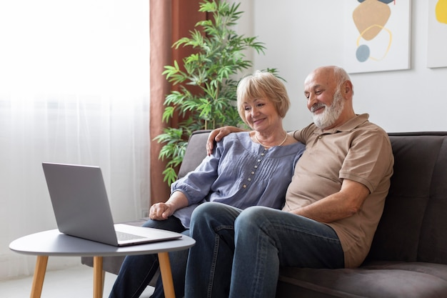 Couple senior shot moyen assis sur le canapé