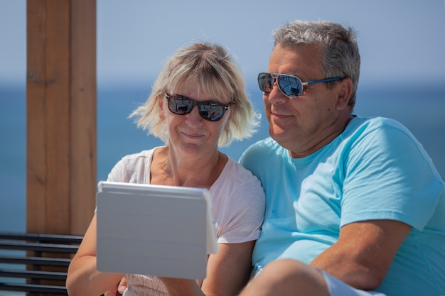Couple senior avec tablette numérique et lunettes de soleil