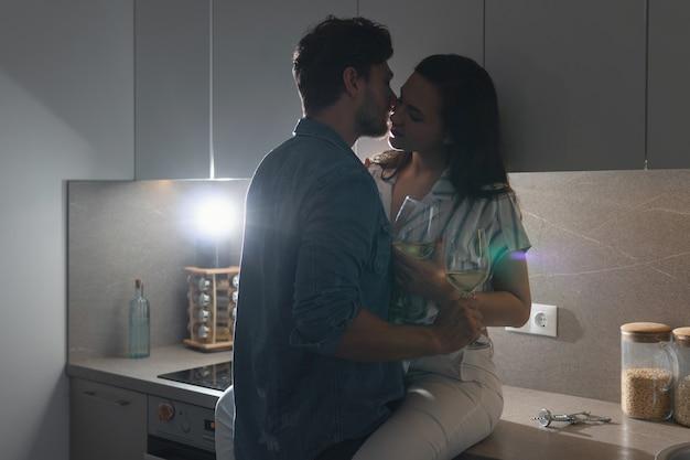 Couple sensuel buvant du vin et se relaxant à la maison