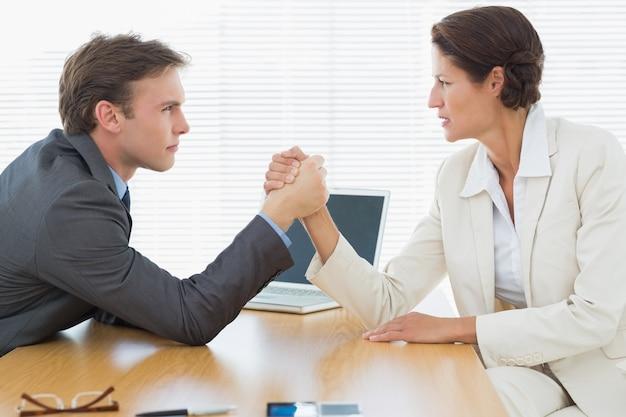Couple sérieux bras bras de fer au bureau