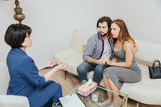 Un couple sérieux est assis ensemble et s'embrasse. ils regardent un psychologue. le docteur leur parle et lui fait un signe de la main.