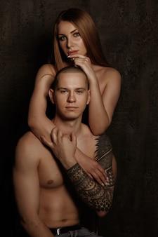 Couple sexy aux seins nus. mec avec un tatouage