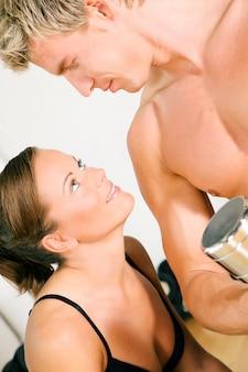 Couple sexy avec des haltères dans la salle de gym
