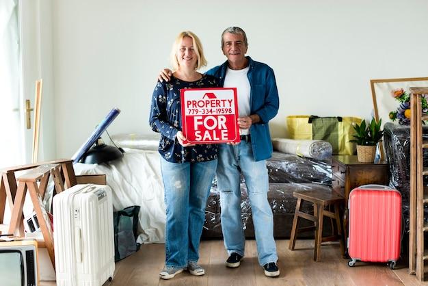 Couple avec un signe de propriété à vendre