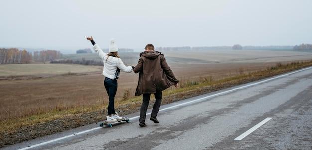 Couple skateboard à l'extérieur ensemble