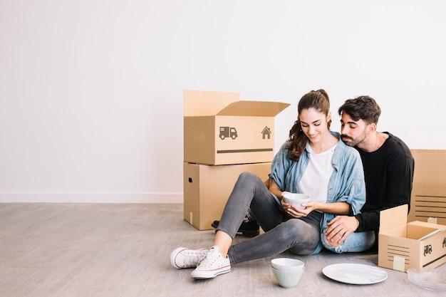 Couple avec smartphone devant des boîtes de déménagement