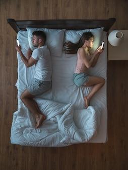 Le couple avec un smartphone était allongé sur le lit. vue d'en-haut