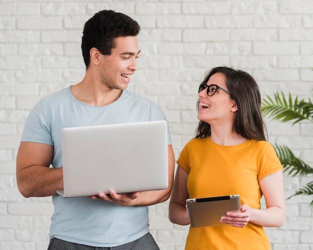 Couple smiley à l'aide d'un ordinateur portable et d'une tablette numérique