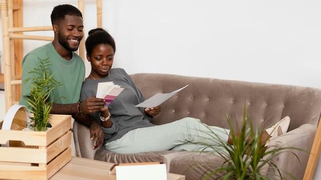 Couple de smiley sur le canapé faisant un plan pour redécorer la maison à l'aide de la palette de couleurs