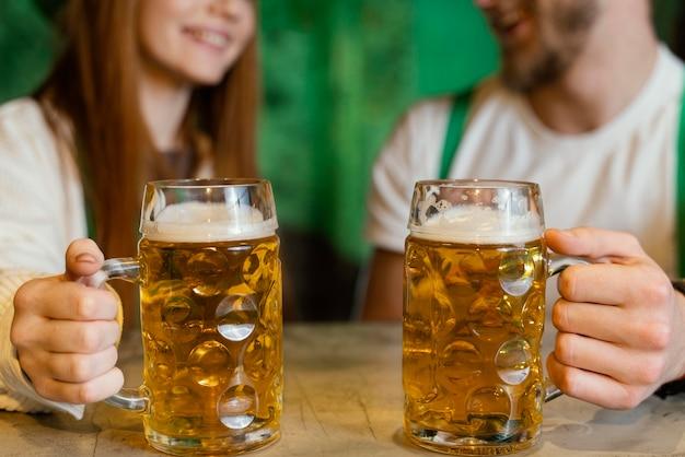Couple smiley célébrant st. le jour de patrick avec des boissons