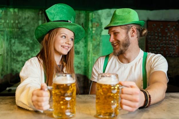 Couple smiley célébrant st. patrick's day au bar avec boissons