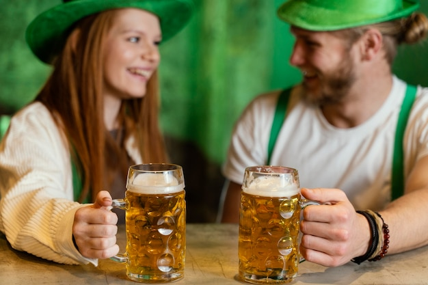 Couple smiley célébrant st. patrick's day avec boissons au bar