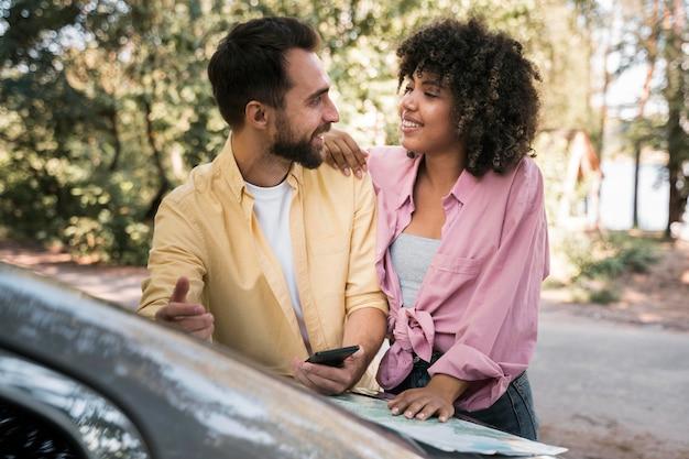 Couple de smiley à l'extérieur avec carte et smartphone